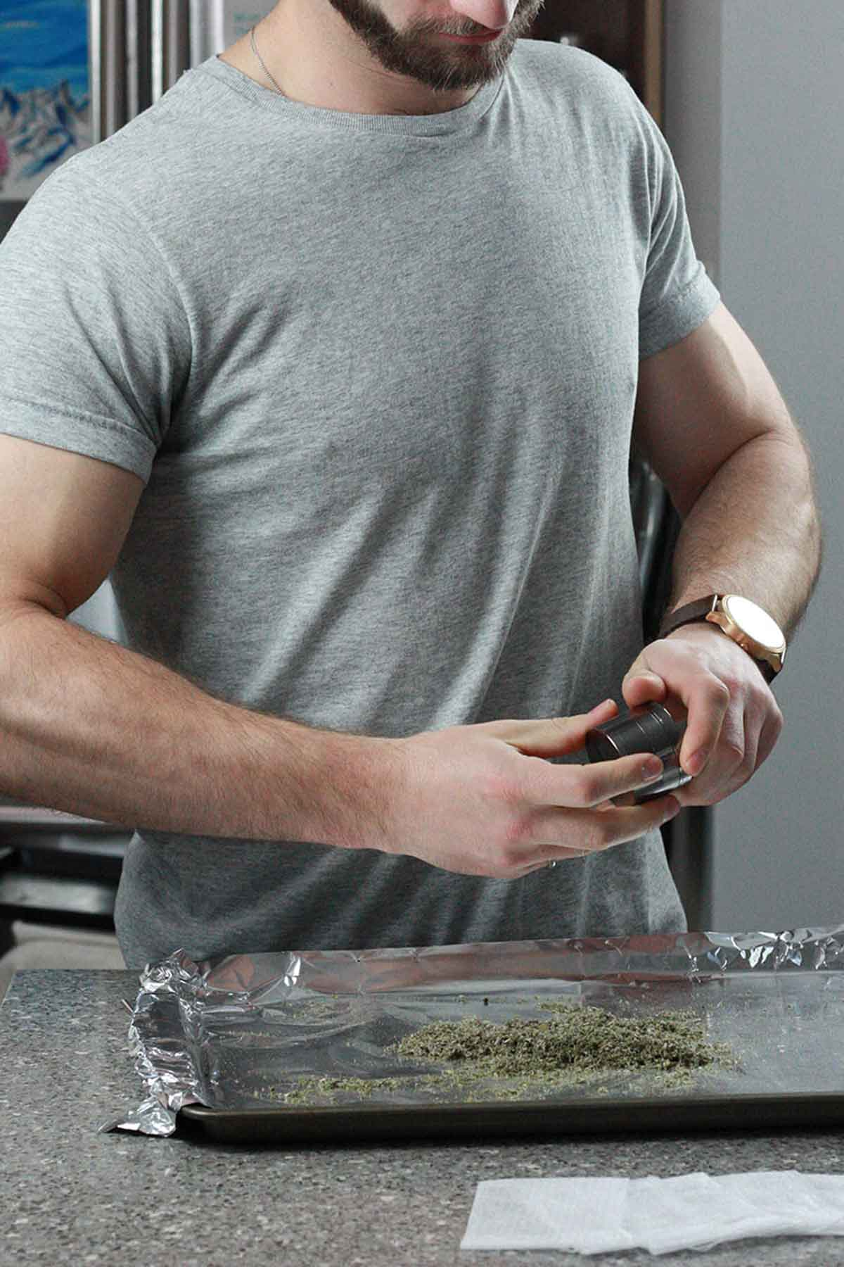 Man grinding cannabis onto a baking sheet to be decarburized in an oven